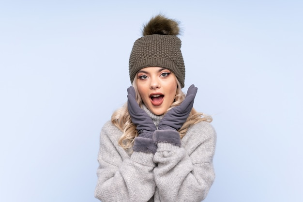 Young teenager girl with winter hat over isolated blue  with surprise facial expression
