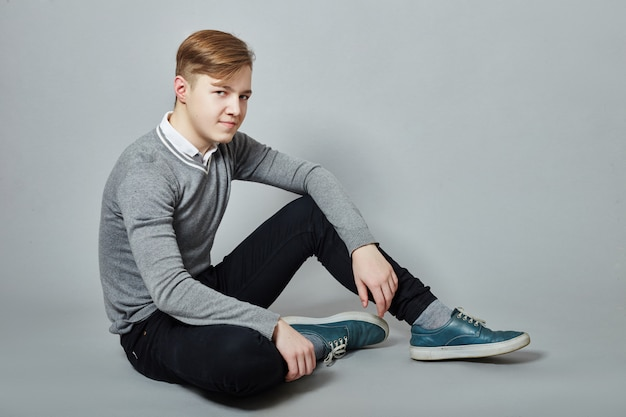 Young teenager guy on the floor denim clothing
