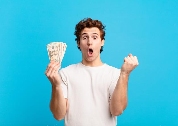Молодой человек-подросток празднует успешную победу и держит долларовые банкноты