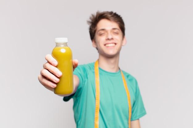 若いティーンエイジャーの男性は幸せな表情となだめるような保持。ダイエットコンセプト