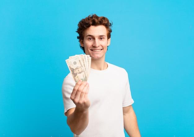젊은 십 대 남자 행복 한 표정과 달러 지폐를 들고