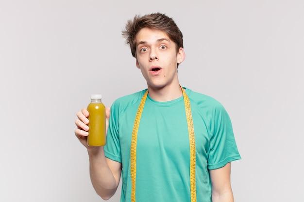 若い10代の男性は、表情を驚かせ、なだめるように保持します。ダイエットコンセプト