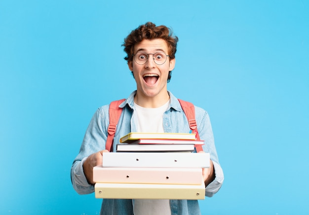 Young teenager man surprised expression. university student concept