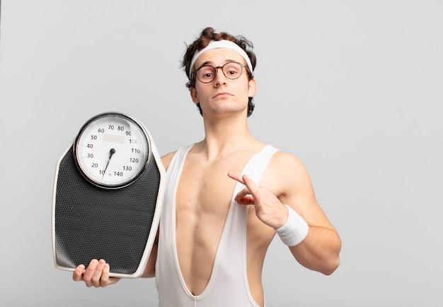 若いティーンエイジャーの男若いクレイジーアスリート幸せな表現と体重計を保持しています