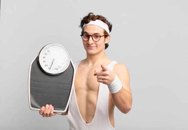 若いティーンエイジャーの男性若いクレイジーアスリートは、体重計を指さしたり、見せたり、保持したりします