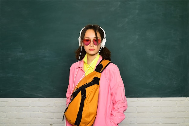 학교 배낭과 헤드폰 어린 십 대 여 학생입니다. 칠판에 십 대 학생입니다.
