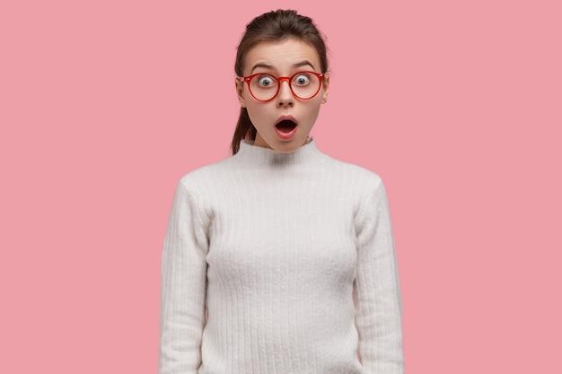 Il giovane adolescente è in preda allo stupore davanti a una scena scioccante, indossa occhiali e abbigliamento casual, è senza parole e sconvolto