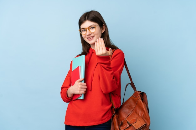 Young teenager student girl holding books over blue wall inviting to come