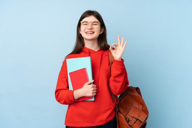 Young  teenager student girl holding a salad over blue wall showing an ok sign with fingers