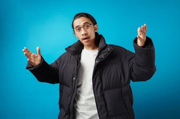 Молодой подросток в куртке делает вопросительный жест на синем фоне