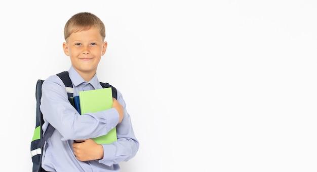白い表面のコピースペースに学校のバックパックを持つ若いティーンエイジャー