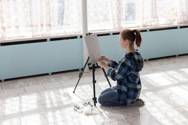 The young teenager woman artist is sitting on the floor of marble tiles. woman in the process of painting with oil paints.