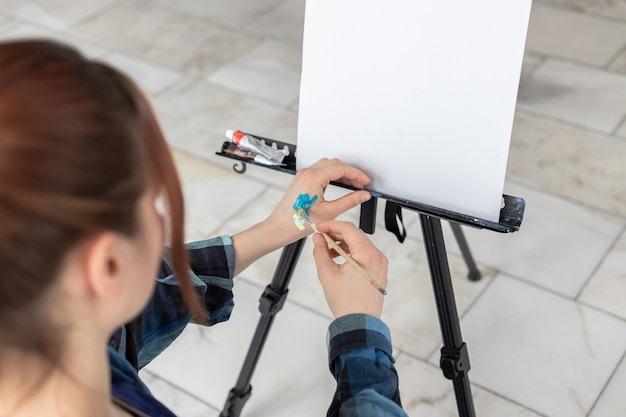 The young teenager woman artist mixes oil paints on her hand. white canvas with copy space is located on the black easel.