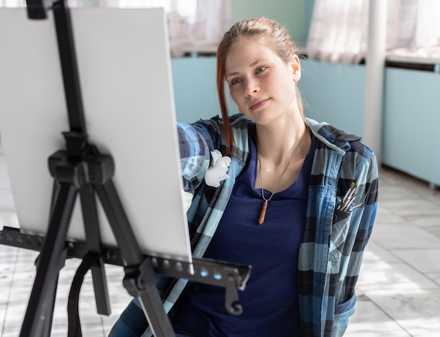 Young teenager woman artist paints with oil paints sitting on the marble floor. white canvas and easel stand on the floor of marble tiles in the room with turquoise and light green walls.
