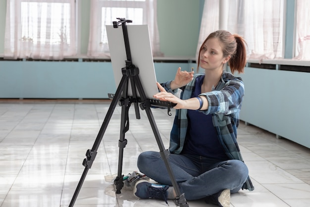 若い10代の女性アーティストは、大理石の床に座って油絵の具でペイントします。白いキャンバスとイーゼルは、ターコイズと明るい緑の壁で部屋の大理石のタイルの床の上に立っています。