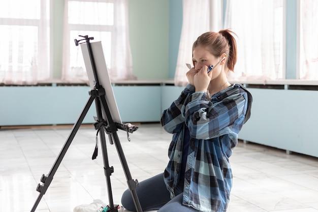 젊은 십 대 여자 아티스트 대리석 바닥에 앉아 오일 페인트로 페인트. 청록색과 연한 녹색 벽이있는 방의 대리석 타일 바닥에 흰색 캔버스와 이젤이 서 있습니다.