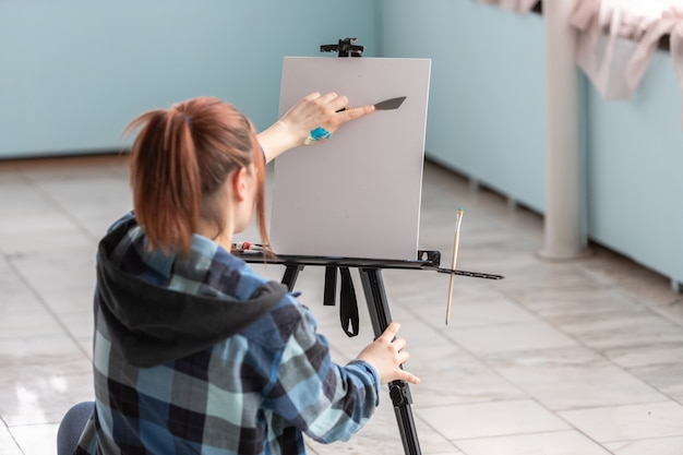A young teenager woman artist with a palette knife in her hands is preparing to paint an oil painting. white canvas with copy space is located on the black easel.