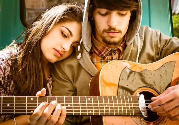 Young teenagers couple in love playing guitar