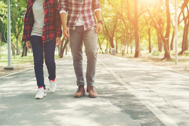 Young teenagers couple walking together in park, relaxing holida