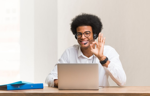 Young telemarketer black man cheerful and confident doing ok gesture