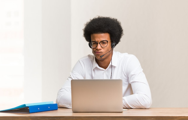 Young telemarketer black man crossing arms relaxed