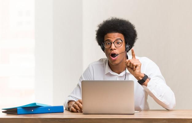 Young telemarketer black man having an idea, inspiration