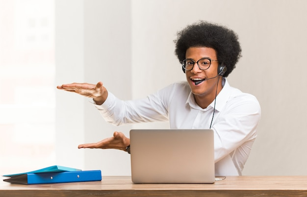 Young telemarketer black man holding something very surprised and shocked