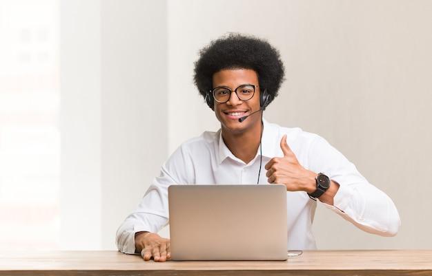 Молодой телемаркетер черный человек улыбается и поднимает палец вверх