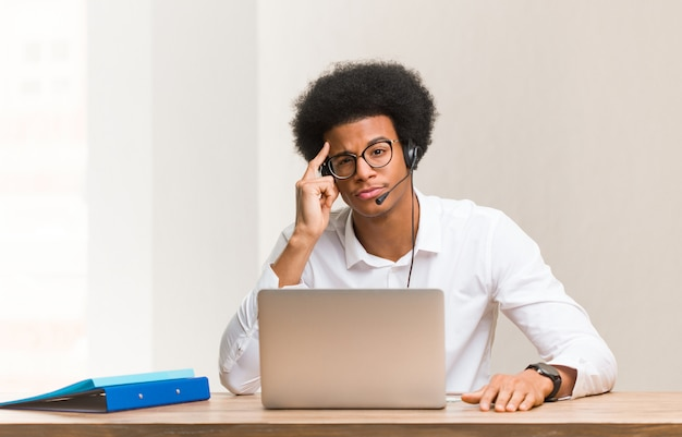 Young telemarketer black man thinking about an idea