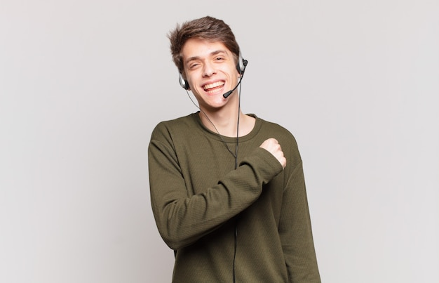 Young telemarketer feeling happy, positive and successful, motivated when facing a challenge or celebrating good results