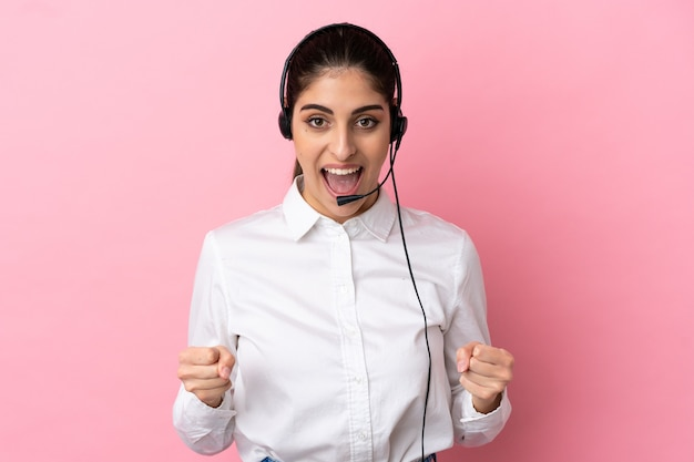 Young telemarketer over isolated background celebrating a victory in winner position