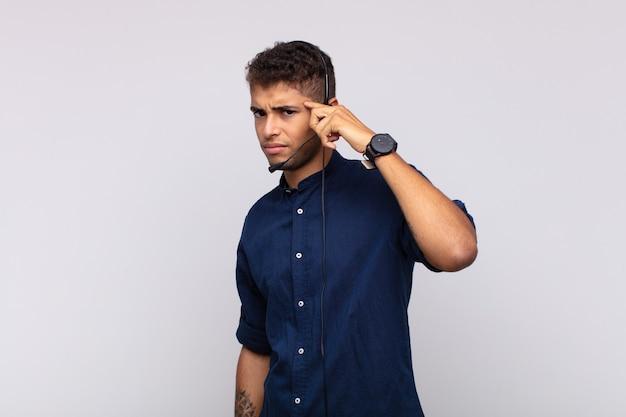Молодой человек, занимающийся телемаркетингом, смущен и озадачен, показывая, что вы сошли с ума, сошли с ума или сошли с ума