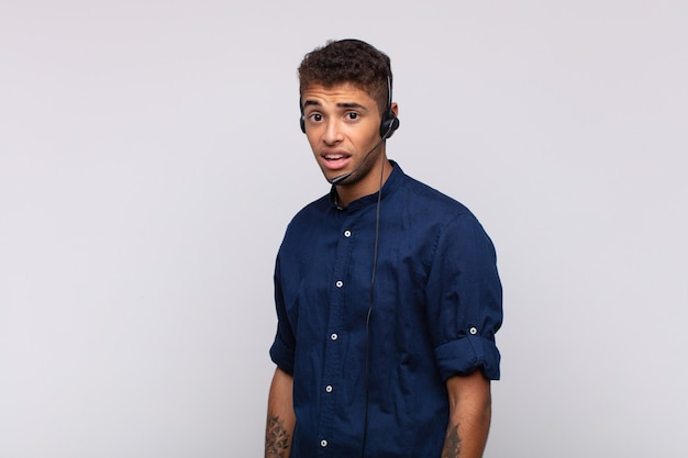 Young telemarketer man feeling puzzled and confused, with a dumb, stunned expression looking at something unexpected