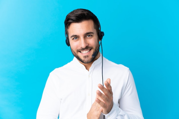 Young telemarketer man over isolated wall