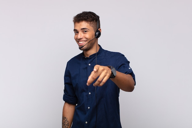 Young telemarketer man pointing at camera with a satisfied, confident, friendly smile, choosing you