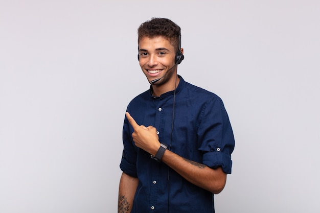 Young telemarketer man smiling cheerfully, feeling happy and pointing to the side and upwards, showing object in copy space