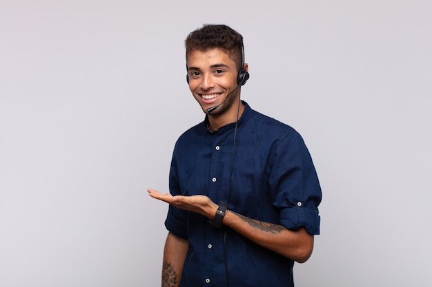 Young telemarketer man smiling cheerfully, feeling happy and showing a concept in copy space with palm of hand