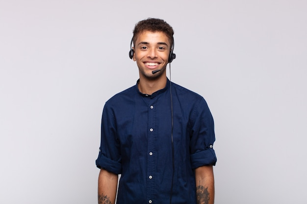 Young telemarketer man smiling happily with a hand on hip and confident, positive, proud and friendly attitude