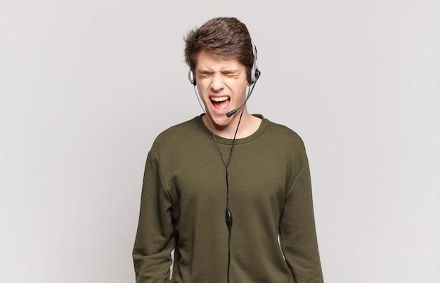 Молодой телемаркетер агрессивно кричит, выглядит очень рассерженным, расстроенным, возмущенным или раздраженным, кричит «нет»