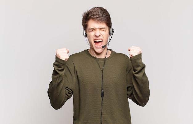 Молодой телемаркетер, агрессивно кричащий с гневным выражением лица или со сжатыми кулаками, празднует успех