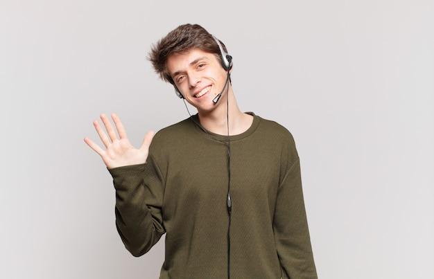 젊은 텔레마케터는 웃고 친근하게 보이며 손으로 5번이나 5번을 앞으로 보여주며 카운트다운