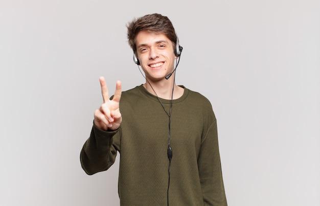 笑顔で幸せそうに見える若いテレマーケティング業者、のんきで前向きで、片手で勝利または平和を身振りで示す