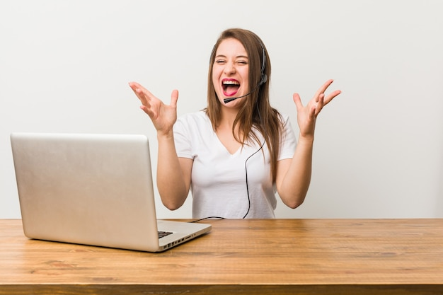 Young telemarketer woman celebrating a victory or success, he is surprised and shocked.
