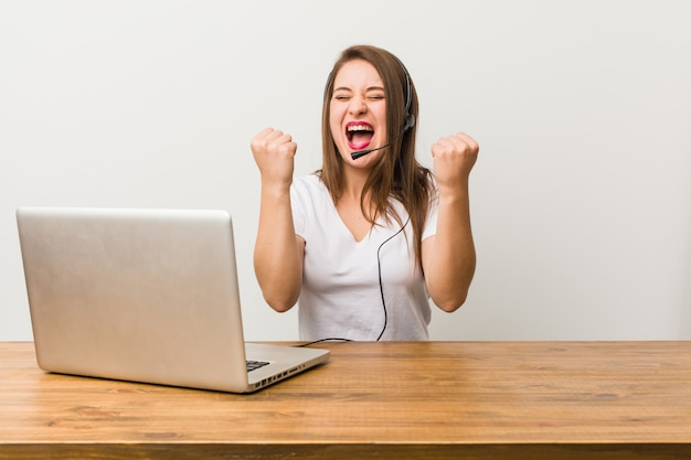 Young telemarketer woman cheering carefree and excited. victory concept.
