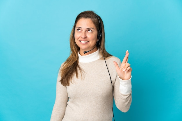 Young telemarketer woman over isolated blue wall with fingers crossing and wishing the best