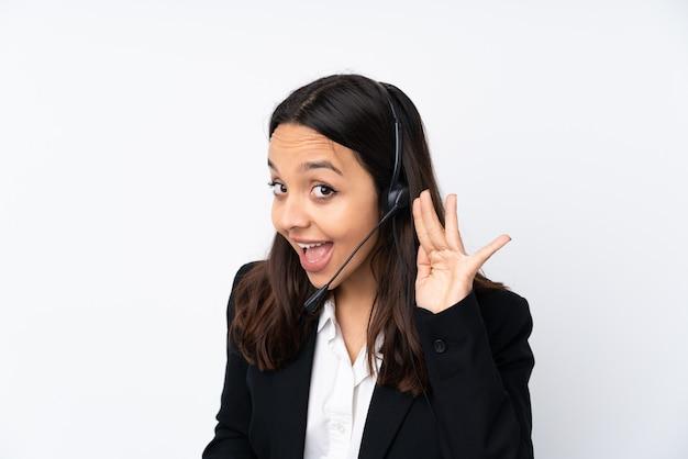 귀에 손을 넣어 뭔가를 듣고 흰 벽에 고립 된 젊은 텔레마케터 여자