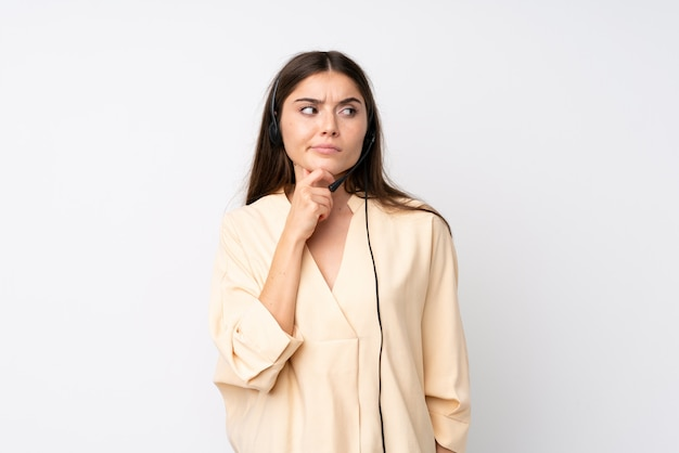 Young telemarketer woman over isolated white wall thinking an idea