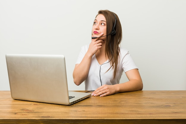 Young telemarketer woman looking sideways with doubtful and skeptical expression.