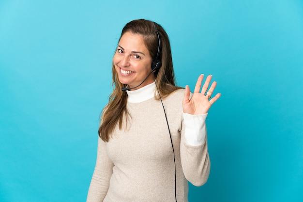 幸せな表情で手で敬礼する孤立した青い上の若いテレマーケティングの女性
