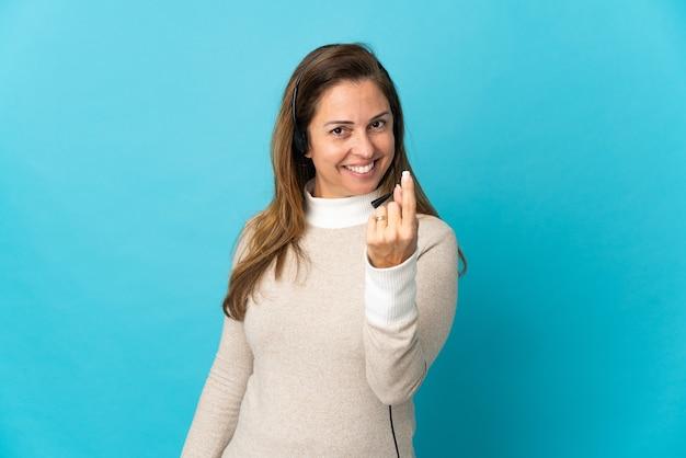 Молодая женщина-телемаркетер над изолированной синей стеной делает приближающийся жест